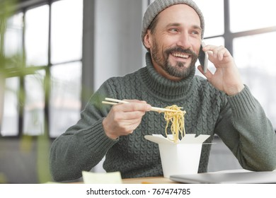Mature bearded male satisfies hunger during break in office, eats delicious pasta uses chopsticks, chatts with friend, shares news between each other, has pleasant talk. , Technolgy, communication