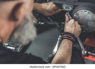 Mature bearded man doing renovation of motorbike