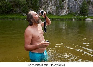 Mature bearded wet man is watching on his waterproof camera during standing in the river.