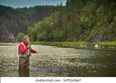 Mature bearded whire wet man is standing in water in the middle of the river and fishing flyfishing, eco tourism.