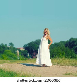 Mature beautiful blonde in a white dress walks on the sandy road on blue sky background
