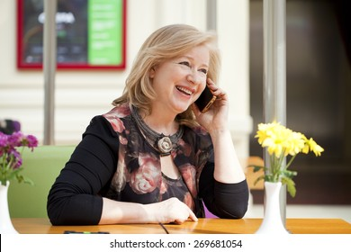 Mature beautiful blonde woman is calling on a cell phone while sitting in a coffee shop
