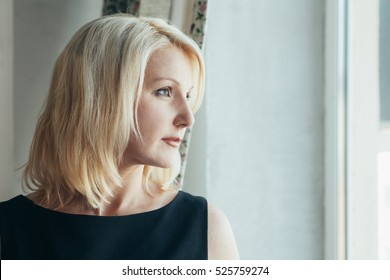 Mature beautiful blonde woman posing in Studio. Portrait in profile with the light from the window