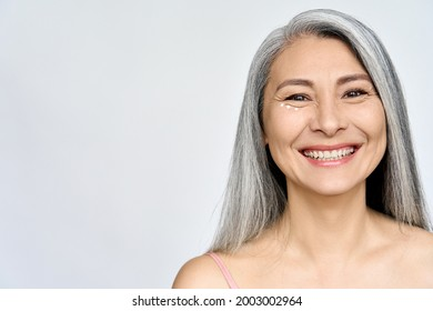 Mature beautiful middle aged asian woman, senior older grey haired lady looking at camera smiling applying under eye antiaging anti wrinkle perfect skin care cream, isolated on white headshot.