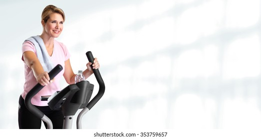Mature beautiful woman doing exercise on elliptical trainer.