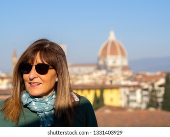 Mature and beautiful woman poses on a terrace and in front of the florentine cathedral, Santa Maria del Fiore y Ponte Vechio
