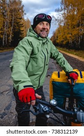 Mature bicycle tourist with his loaded bike on an asphalt autumn road