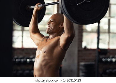 Mature black bodybuilder doing weight lifting at gym. Muscular african american guy doing heavy deadlift exercise at gym. Determined strong man doing exercises at biceps and shoulders.