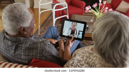 Mature black couple consulting doctor on a tablet
