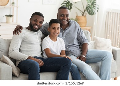 Mature Black Man Posing At Home With His Son And Grandson, Smiling At Camera, Sitting On Couch In Living Room, Bonding Together