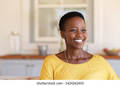 Mature black woman with short curly hair smiling and looking away. Closeup face of happy young woman relaxing at home under the patio. Beautiful carefree lady smiling with hope and copy space.