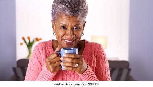 Mature black woman smiling with coffee mug