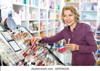 Mature blond woman choosing lip plumper on display and smiling