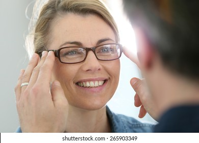 Mature blond woman with optician trying eyeglasses