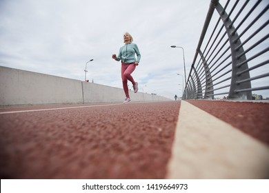 Mature blonde female in sportswear moving along border while running down racetrack on outdoor stadium in the morning