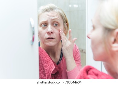 Mature blonde woman checking her wrinkles and under eye circles, not satisfied with her looks