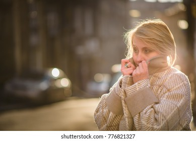 Mature blonde woman feeling cold in the street, tucking her coat closely to her face, autumn or winter surrounding