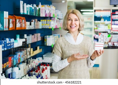 Mature blonde woman near counter in pharmacy drugstore