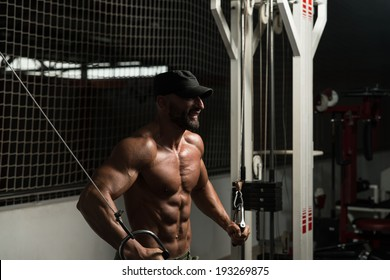Mature Bodybuilder Is Working On His Chest With Cable Crossover In A Dark Gym