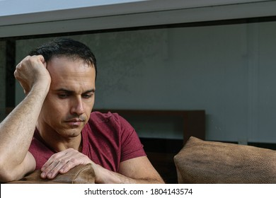 Mature Brazilian man (44 years old) sitting on the brown sofa, behind the glass, sad and crestfallen.