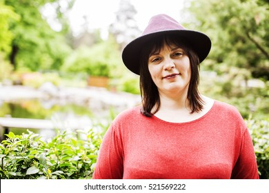 mature brunette fat woman in green garden wearing hat, smiling, friendly welkoming, lifestyle people concept close up