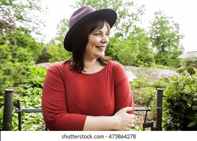 mature brunette woman in green garden wearing hat, smiling, friendly welkoming, lifestyle people concept close up