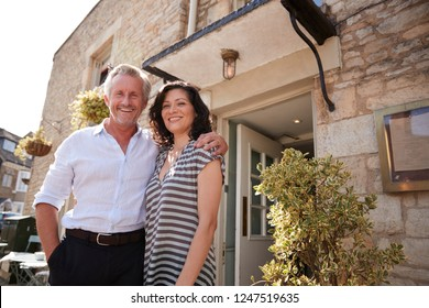 Mature business couple standing outside their restaurant pub