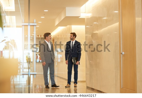 Mature business executive standing in a modern office building foyer, talking with a stylish young employee
