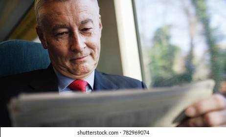 Mature business investor reading a newspaper during a train journey