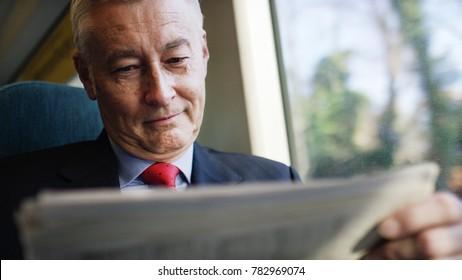 Investidor de negócios maduro lendo um jornal durante uma viagem de trem