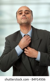 an mature business man adjusting his tie