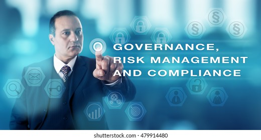 Mature business man with focused gaze is pushing a virtual button to activate GOVERNANCE, RISK MANAGEMENT AND COMPLIANCE onscreen. Business concept for corporate governance, laws and regulations.