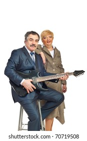 Mature business man in formal wear playing electronic guitar and being assisted by a woman isolated on white background
