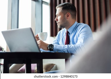 Mature business man having a coffee in a coffee shop and working on his laptop