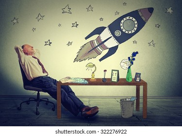 Mature business man relaxing at desk in his office. Happy senior businessman sitting on armchair daydreaming of corporate company prosperity. Future space tourism ambition concept