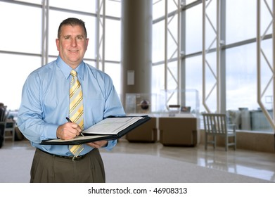A mature business man taking notes in a large lobby