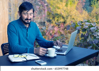 Mature Business Person in smart casual Clothing sitting at wooden Table in front of Computer drinking Morning Coffee and smiling