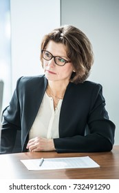 Mature business woman in flasses sitting at meeting table in office