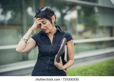Mature business woman having a headache, returning home from work
