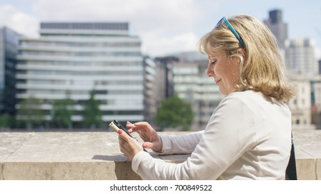 Mature business woman on her phone outdoors in the city