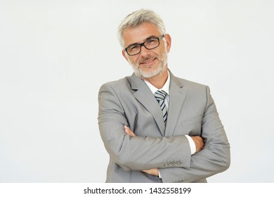 Mature businessman with arms crossed on white background