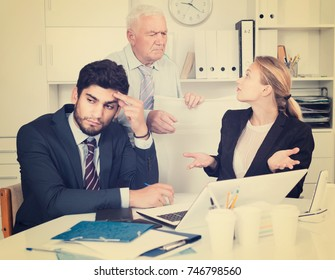 Mature businessman is chastising employees because of uncompleted work in the office.