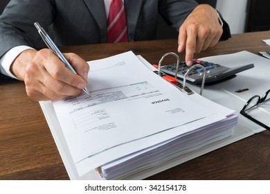 Mature businessman checking receipts with calculator at desk