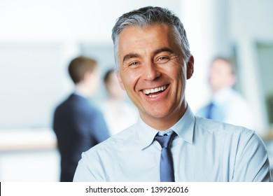 Mature businessman with colleagues in the background