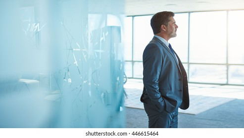 Mature businessman in a corporate suit standing in a large empty office space with modern glass room divider and looking away through large windows optimistically