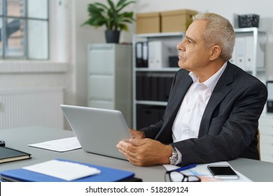 Mature businessman at desk looking toward window in office with binders on bookshelf in background