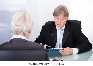 Mature Businessman Discussing With Businesswoman In Meeting