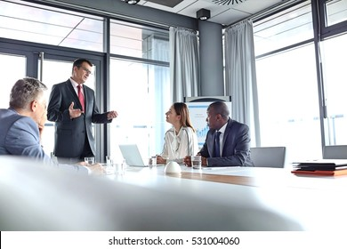 Zralý podnikatel diskutuje s kolegy ve správní místnosti