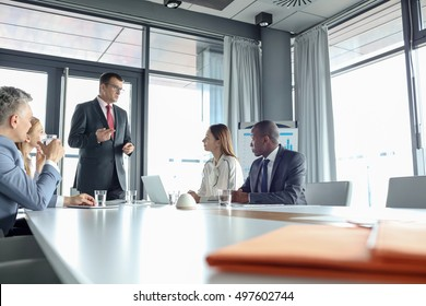 Mature businessman discussing with colleagues in meeting room