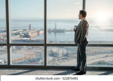 Mature businessman drinking a coffee and looking out of a window at the city skyline from an office building